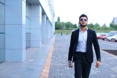 Арабский парень в деловом центре стоит усмехаясь идти медленный Стоковые Изображения