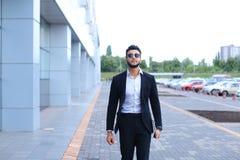 Арабский парень в деловом центре стоит усмехаясь идти медленный Стоковые Фото