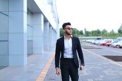 Арабский парень в деловом центре стоит усмехаясь идти медленный Стоковая Фотография