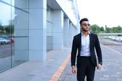 Арабский парень в деловом центре стоит усмехаясь идти медленный Стоковое фото RF