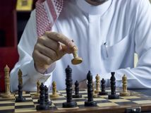 Арабский человек играя шахмат на его столе 1 стоковая фотография rf
