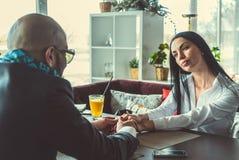 Арабский человек и девушка держа руки в ресторане стоковое фото rf
