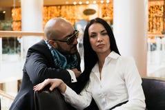 Арабский человек и стильная девушка сидят на софе стоковое изображение rf