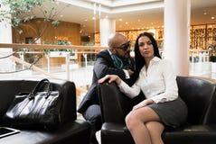 Арабский человек и стильная девушка сидят на софе стоковые фото