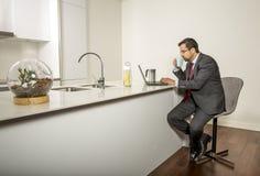 Арабский человек woking в его компьтер-книжке в кухне Стоковое Изображение RF