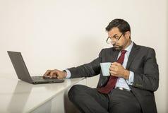 Арабский человек woking в его компьтер-книжке в кухне Стоковые Фото