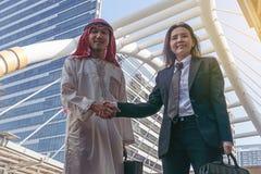 Арабский handshaking бизнесмена и коммерсантки Стоковое фото RF