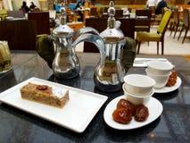 2 арабских бака кофе, чашки, даты, торт на таблице в кафе Стоковые Изображения