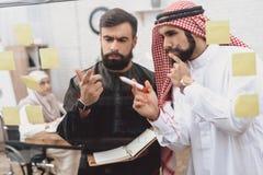 2 арабских люд работая в офисе Сотрудники принимают примечания на стеклянной доске Стоковая Фотография RF