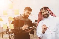 2 арабских люд работая в офисе Сотрудники принимают примечания перед стеклянной доской Стоковое Фото