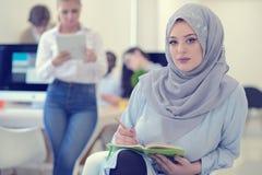 Аравийская коммерсантка в startup офисе при команда работая на заднем плане, Стоковые Фото