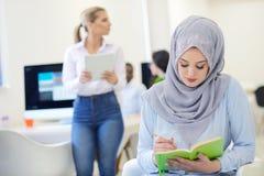 Аравийская коммерсантка в startup офисе при команда работая на заднем плане, Стоковое Фото
