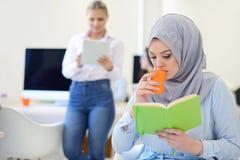 Аравийская коммерсантка в startup офисе при команда работая на заднем плане, Стоковое фото RF