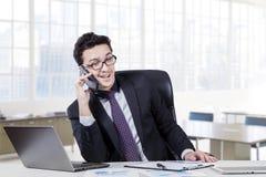 Аравийский бизнесмен говоря на телефоне в офисе Стоковые Изображения RF