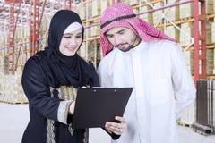 Аравийский взгляд работников на документе в складе Стоковые Изображения RF