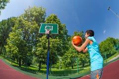 Аравийский мальчик держит шарик для того чтобы бросить в цель баскетбола Стоковые Изображения