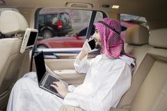 Аравийский работник говоря на мобильном телефоне в автомобиле Стоковые Изображения RF