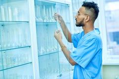Аравийский ученый кладя склянки в кухонный шкаф стоковые фото