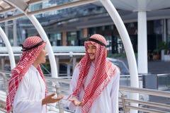 2 аравийских бизнесмена обсуждают и идут совместно вокруг современного Стоковое Изображение