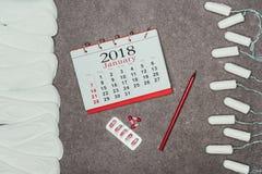 Аранжированные менструальные пусковые площадки и тампоны, календарь и пилюльки на серой поверхности Стоковая Фотография RF