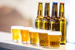 Аранжированные стекла и бутылки пива на счетчике бара Стоковые Изображения RF