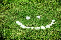 Аранжировать белый камень на зеленой траве в концепции улыбки для ec стоковое фото