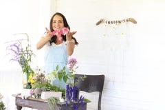 Аранжировать молодой женщины высушенные цветки дома стоковые фотографии rf