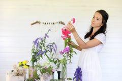 Аранжировать молодой женщины высушенные цветки дома стоковое изображение rf