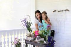 Аранжировать молодой женщины высушенные цветки дома стоковые изображения