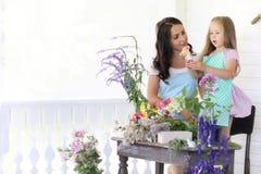 Аранжировать молодой женщины высушенные цветки дома стоковые изображения rf