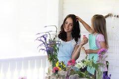 Аранжировать молодой женщины высушенные цветки дома стоковое изображение