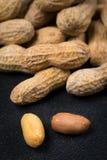 2 арахиса без раковин перед кучей арахисов закрывают вверх Стоковые Фото