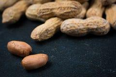 2 арахиса без раковин перед кучей арахисов Стоковое Изображение