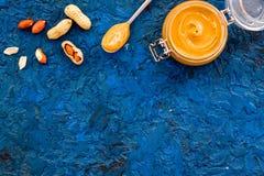 Арахисовое масло в стеклянном опарнике около арахиса на голубом космосе экземпляра взгляд сверху предпосылки Стоковая Фотография RF