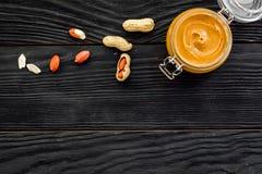 Арахисовое масло в стеклянном опарнике около арахиса на черном деревянном космосе экземпляра взгляд сверху предпосылки Стоковая Фотография RF