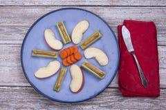 Арахисовое масло заполнило сельдерей, морковей и куски яблока Стоковое фото RF