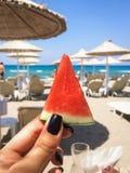 Арбуз в руках девушки на пляже на предпосылке моря Стоковая Фотография RF