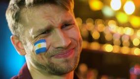 Аргентинский мужской вентилятор раздражанный с национальной потерей футбольной команды, флаг на щеке сток-видео