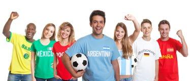 Аргентинский сторонник футбола с шариком и вентиляторы от другого подсчитывают стоковые фото
