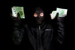 Арестованный похититель в балаклаве с украденными деньгами и поднятыми оружиями Стоковые Фото