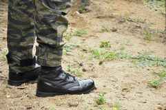 Армия, войска носки солдата камуфлирует положение на поле травы Стоковые Изображения RF