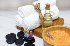 Ароматичное масло, мягкие полотенца, горячие камни и соль для принятия ванны в деревянном шаре с ложкой составляют комплект для п Стоковая Фотография