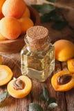 Ароматичное масло абрикоса в конце-вверх стеклянной бутылки вертикально Стоковая Фотография RF