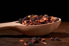 ароматичный сухой чай с плодоовощами и лепестками в ложке, на деревянной предпосылке Концепция уюта стоковое изображение rf