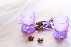 2 ароматичных свечи в стеклянных подсвечниках с бумагой, циннамоном и анисовкой лаванды на конце таблицы вверх Стоковая Фотография