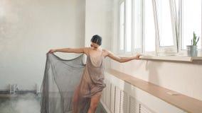 Артист балета в платье летая ткани, как фантастическая нимфа поднимая ее ногу вверх сток-видео