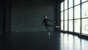 Артист балета в студии молодой человек делает высокий прыжок и красиво танцует на темной предпосылке движение медленное сток-видео