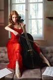 Артист балета в красном платье и pointe играя на античной черной виолончели стоковые изображения