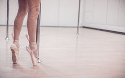 Артист балета стоя в Pointe около поляка в пустой студии с деревянным полом Конец-вверх Стоковые Изображения RF