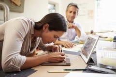 2 архитектора делая модели в офисе используя таблетку цифров Стоковая Фотография RF